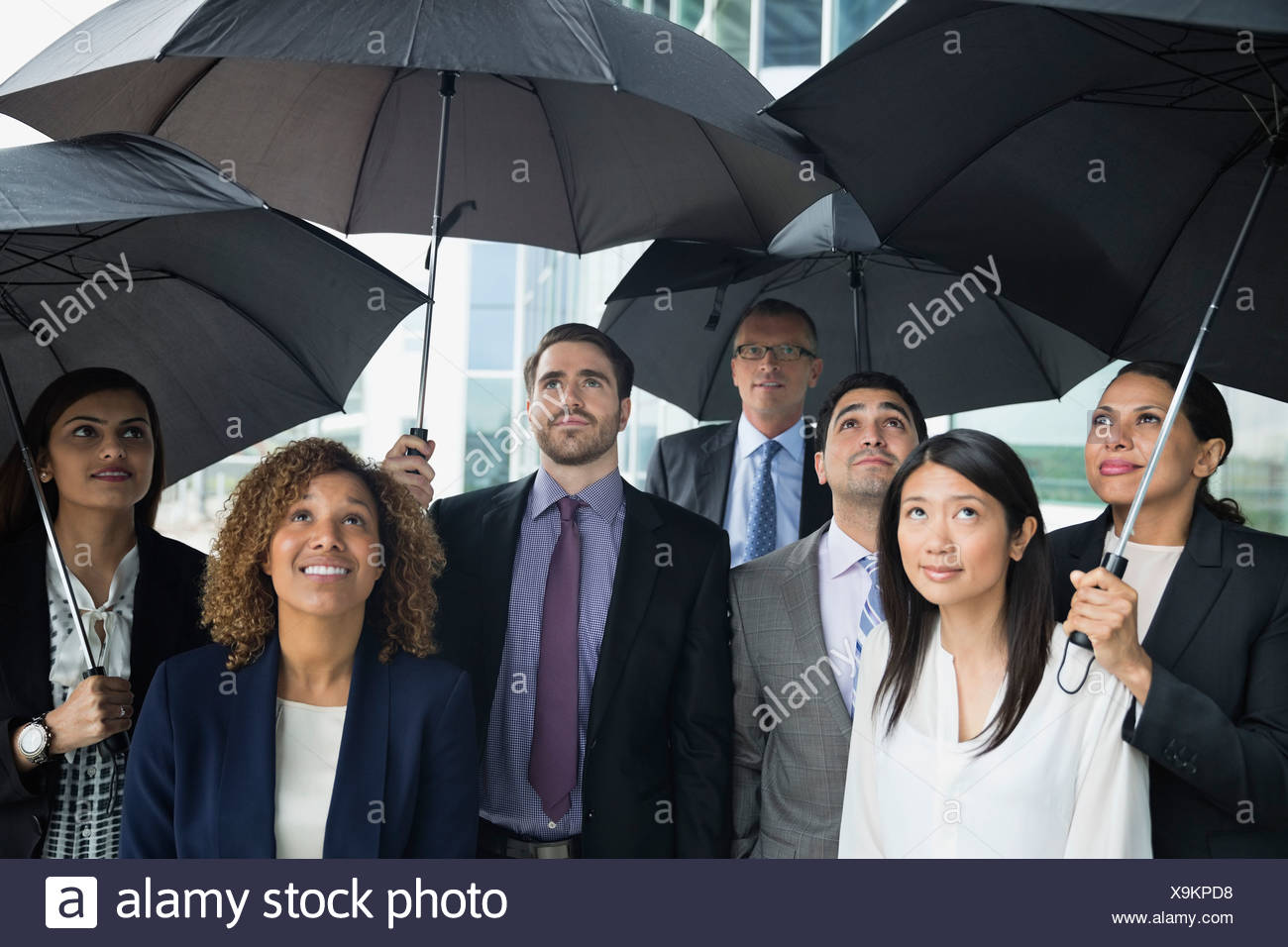 Business team with umbrellas looking up - Stock Image