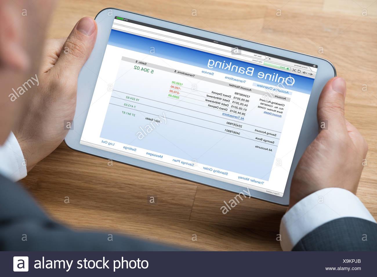 Businessman Doing Online Banking On Digital Tablet - Stock Image