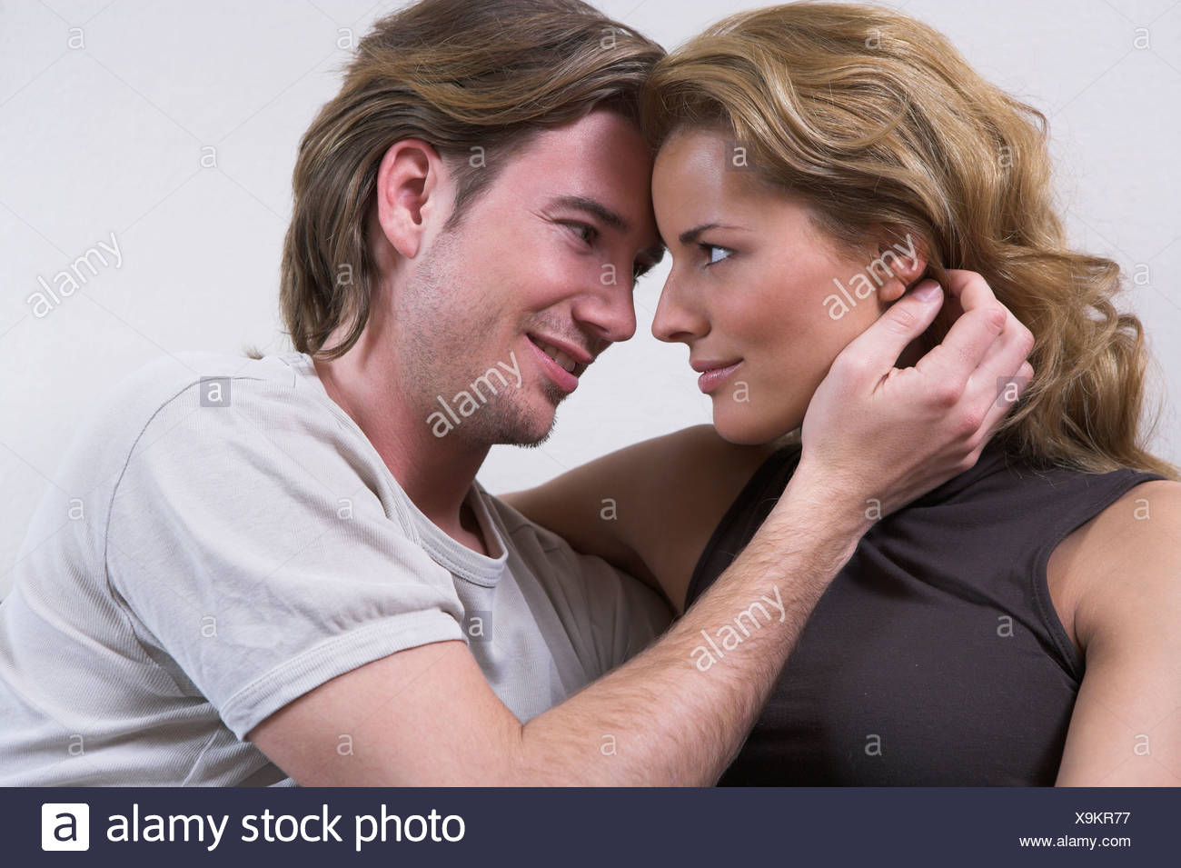 portrait of young couple tenderly looking at each other - Stock Image