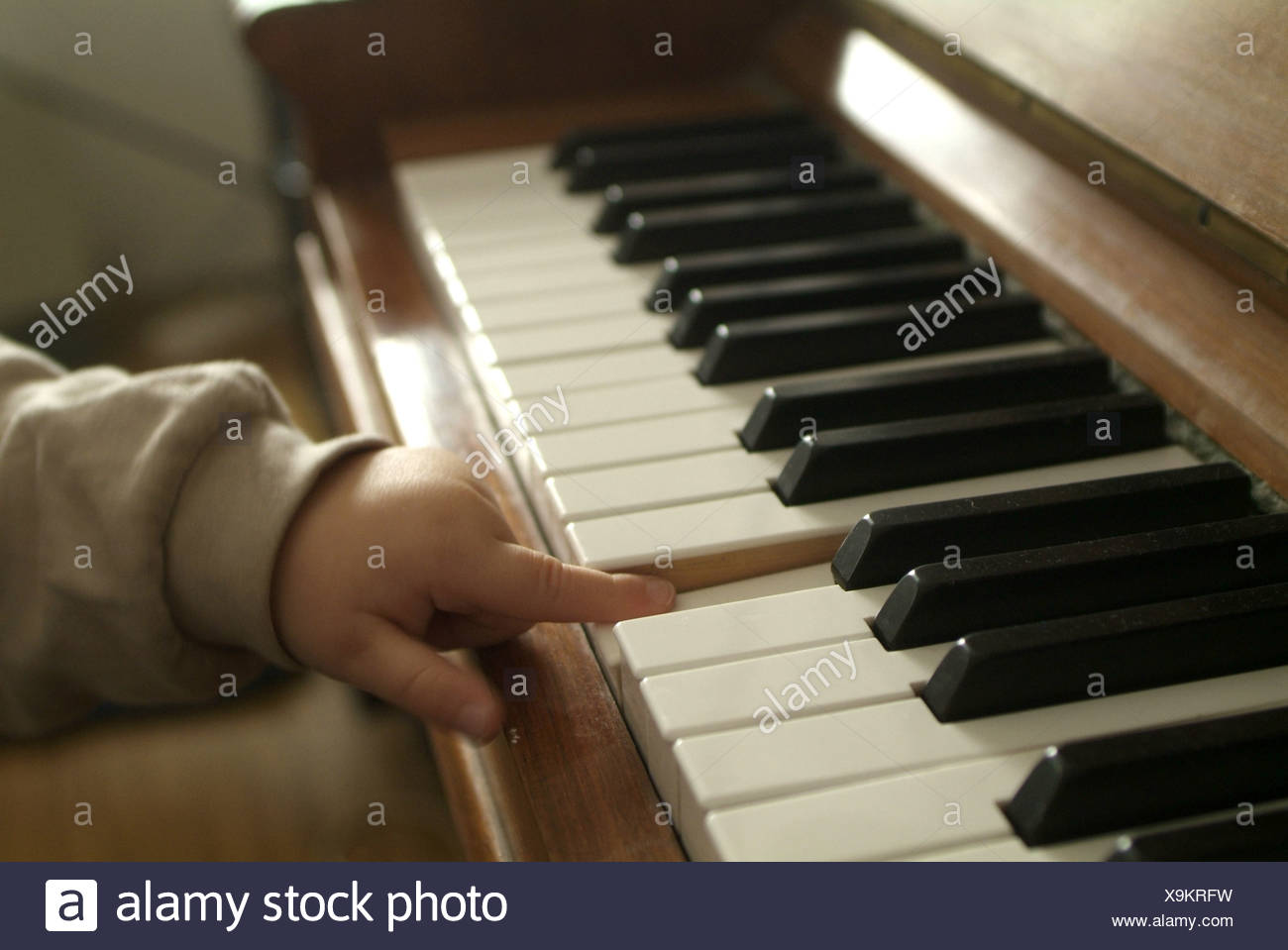 Two years old boy is interested for the piano and played on the keys. - Stock Image