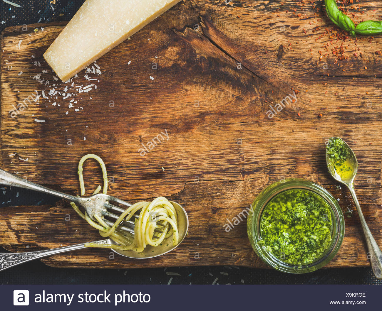 Italian cuisine cooking background. Jar with pesto sauce, spoon and fork with cooked spaghetti, fresh basil leaves and Parmesan - Stock Image