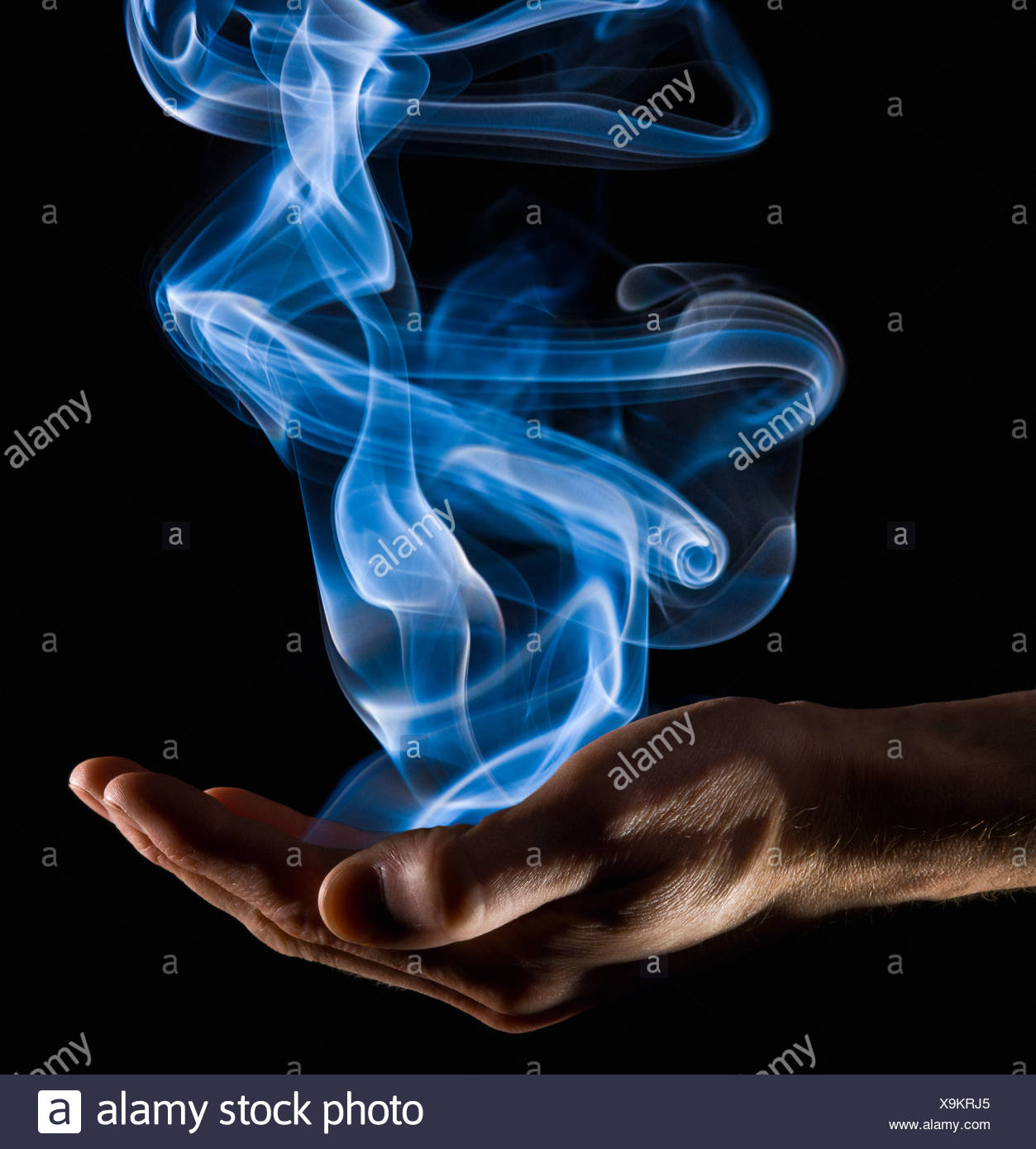 Smoke rising from a hand - Stock Image