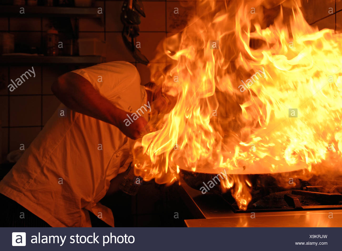 Cook holding a burning pan on the stove - Stock Image