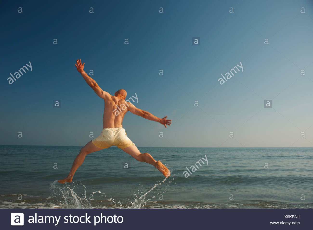 Mid adult man jumping outstretched over sea - Stock Image
