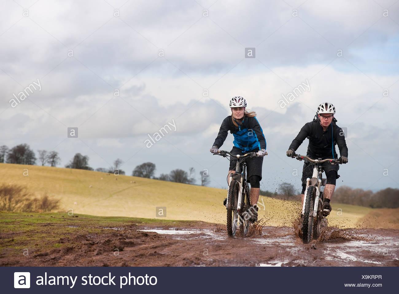 Couple riding bike through muddy puddles - Stock Image