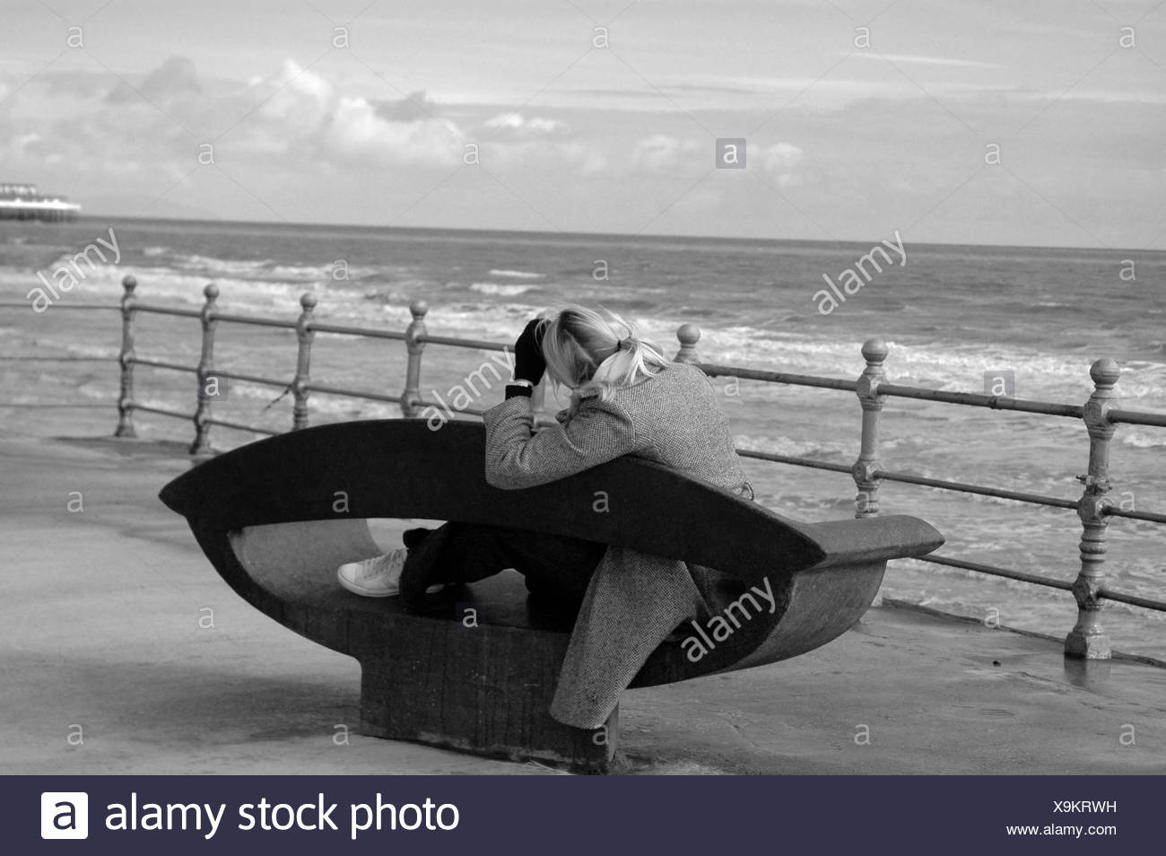 Girl on bench looking out at sea - Stock Image
