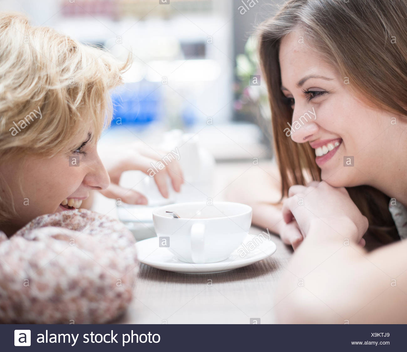 Side view of smiling young female friends looking at each other in cafe - Stock Image