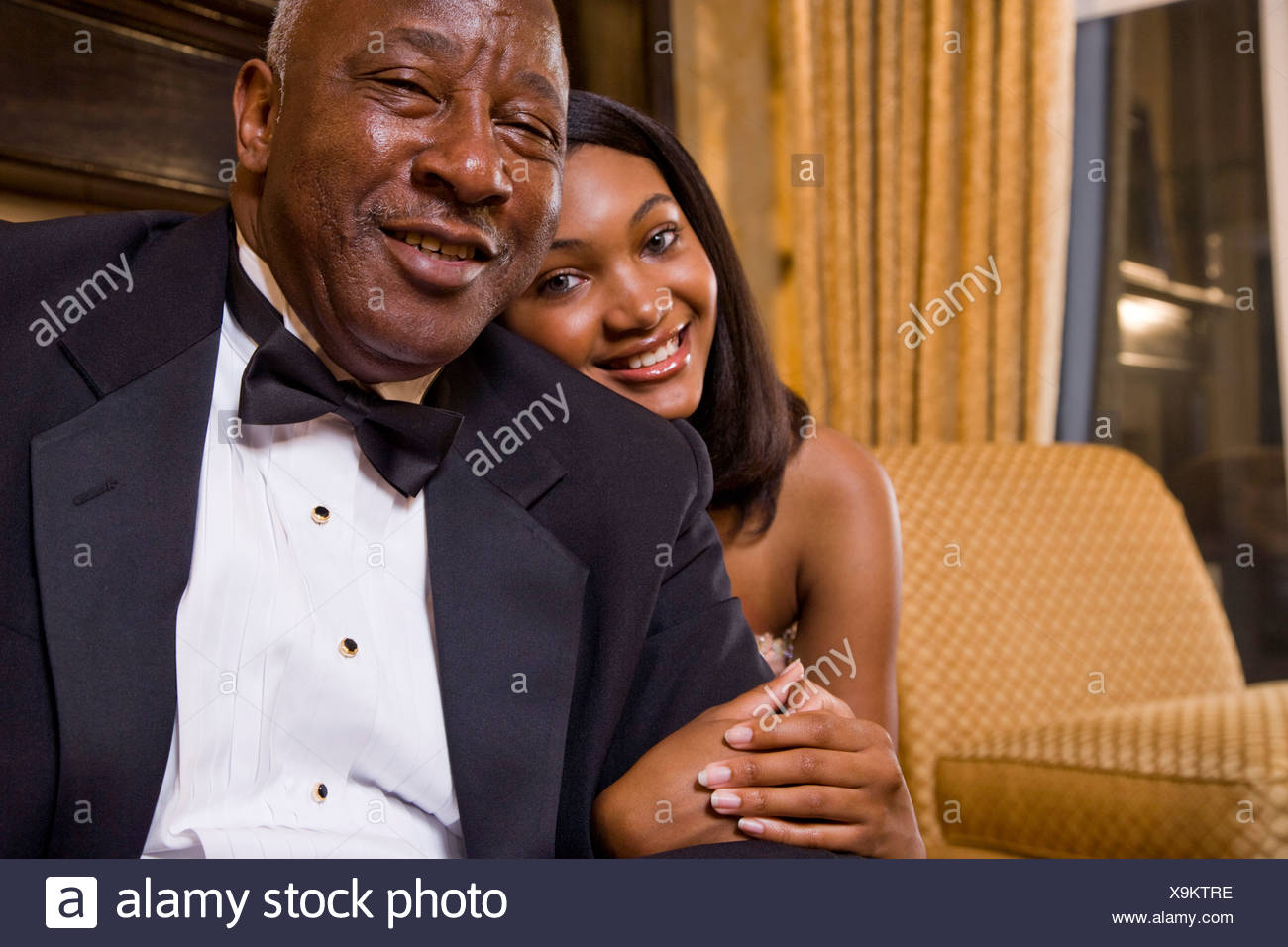 3c87ddff396 Teenage girl posing with grandfather in formal attire at home Stock ...