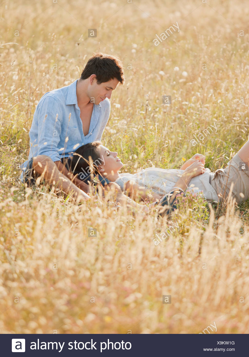Smiling couple relaxing in wheatfield Stock Photo