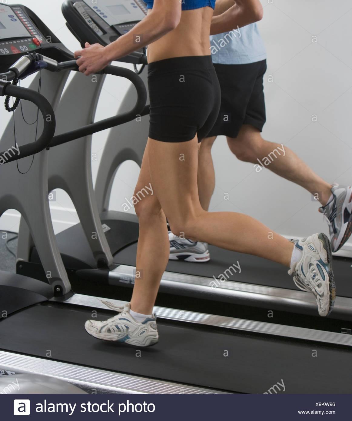 Couple running on treadmills - Stock Image