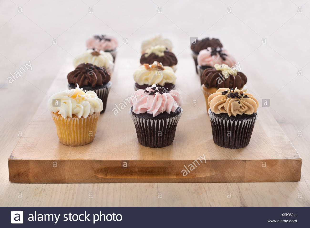 Assorted dozen cupcakes on wooden cutting board. Light wood, bright setting. Stock Photo
