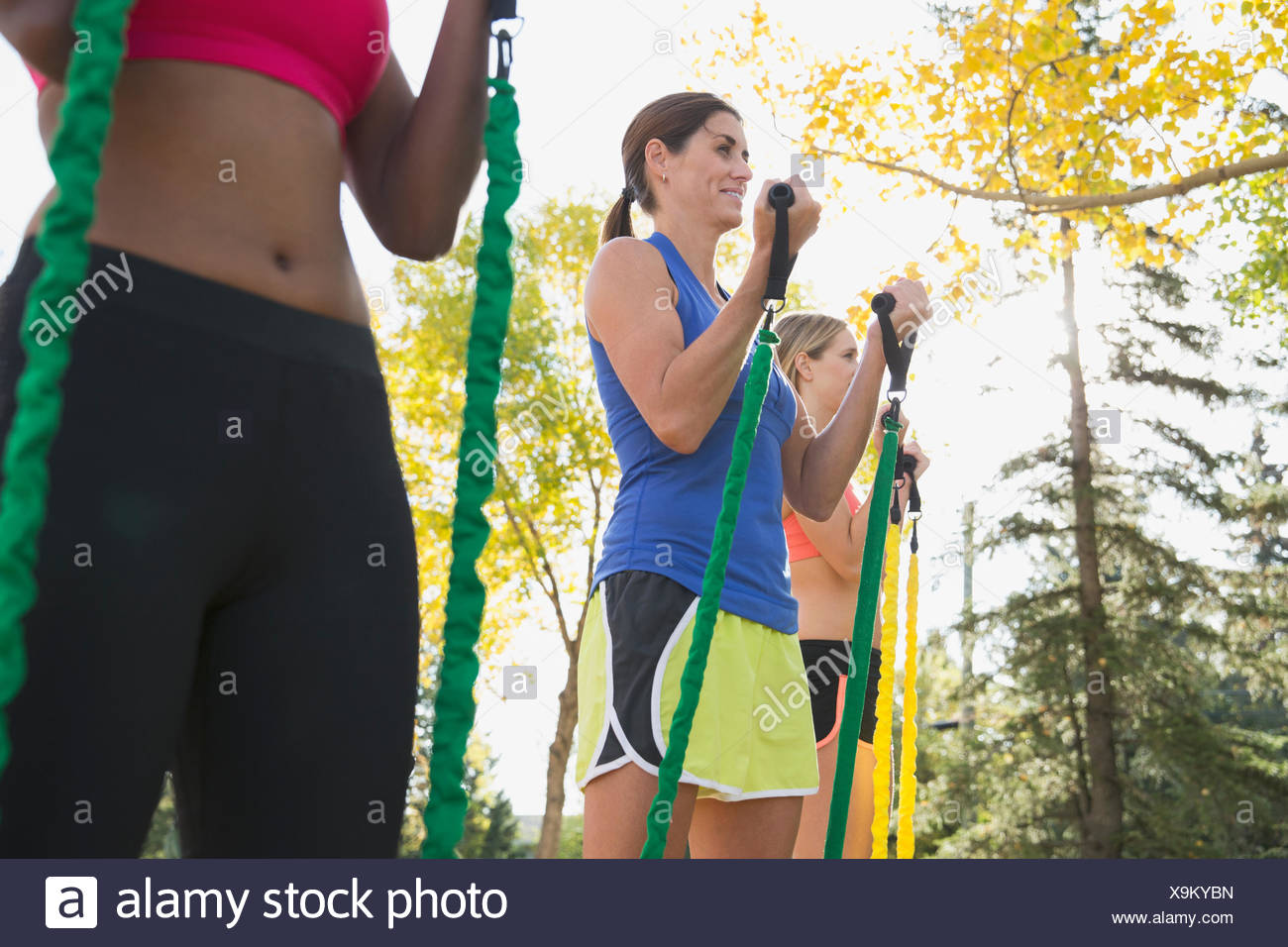 Women using resistance bands at outdoor fitness class. - Stock Image