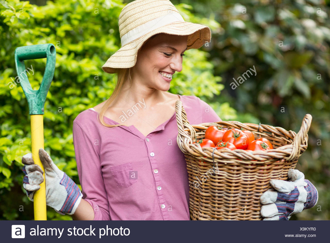 Happy gardener holding tomato basket and work tool - Stock Image