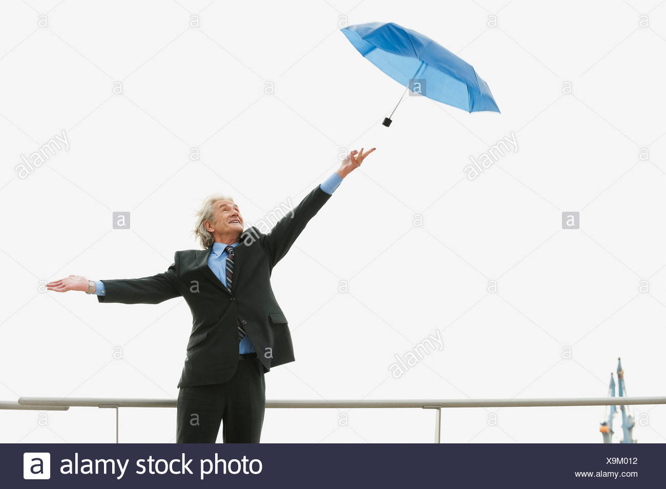 Germany, Hamburg, Businessman trying to catch fly-away umbrella - Stock Image