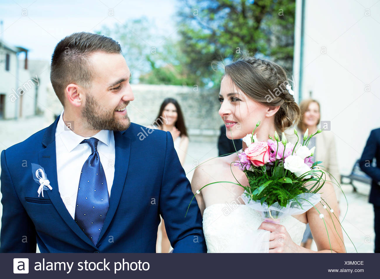 Bride and groom walking with wedding guests in background - Stock Image