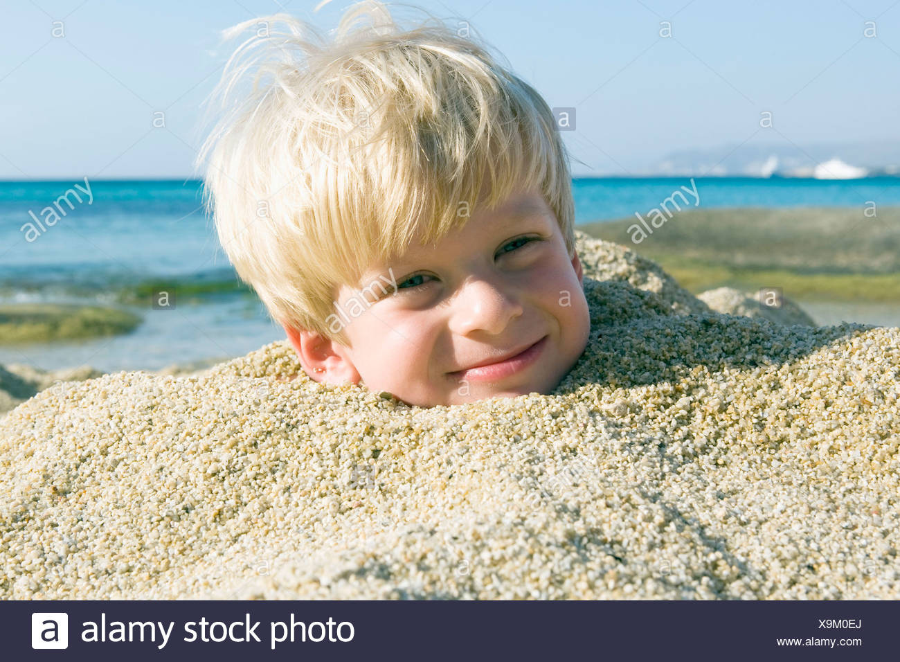 Young boy buried in the sand smiling. Stock Photo