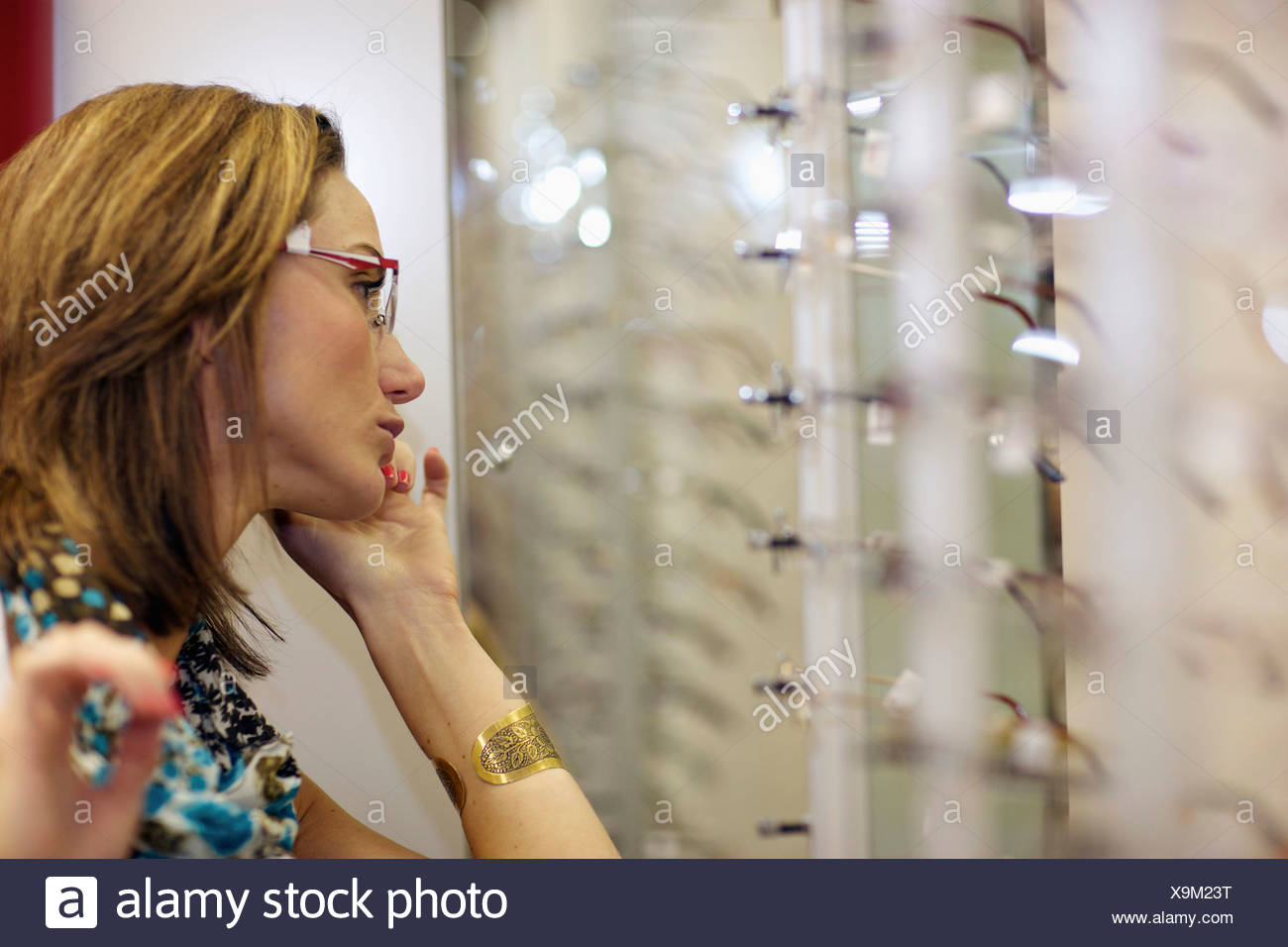 A young woman trying on spectacles, Pietermaritzburg, KwaZulu-Natal, South Africa - Stock Image