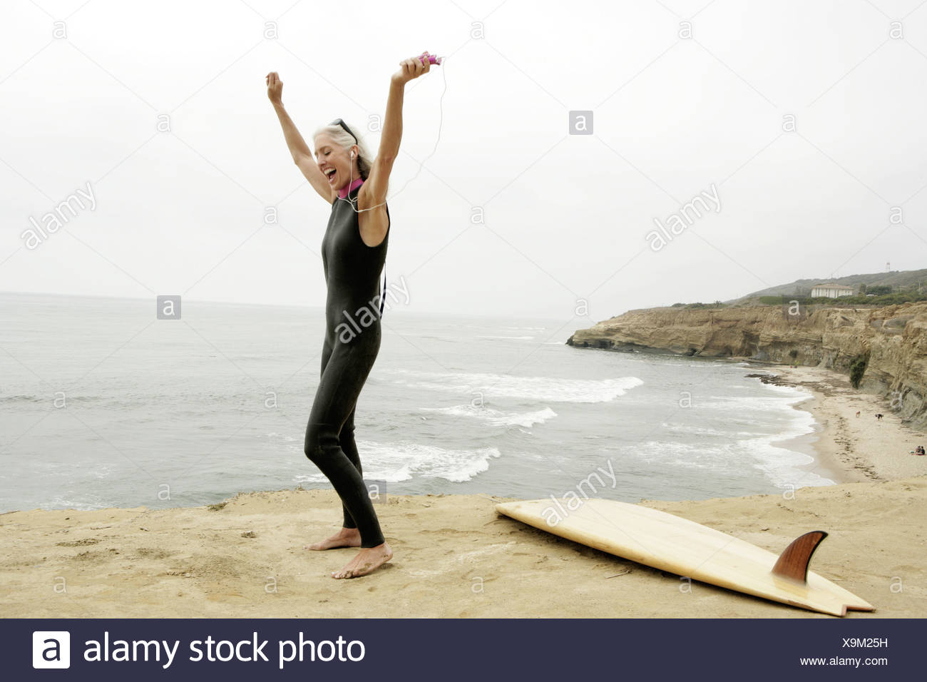 View of a woman rejoicing on a shore. - Stock Image