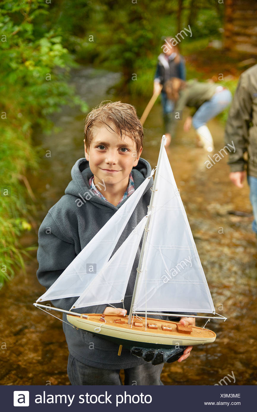 Young boy holding sailing boat in river Stock Photo