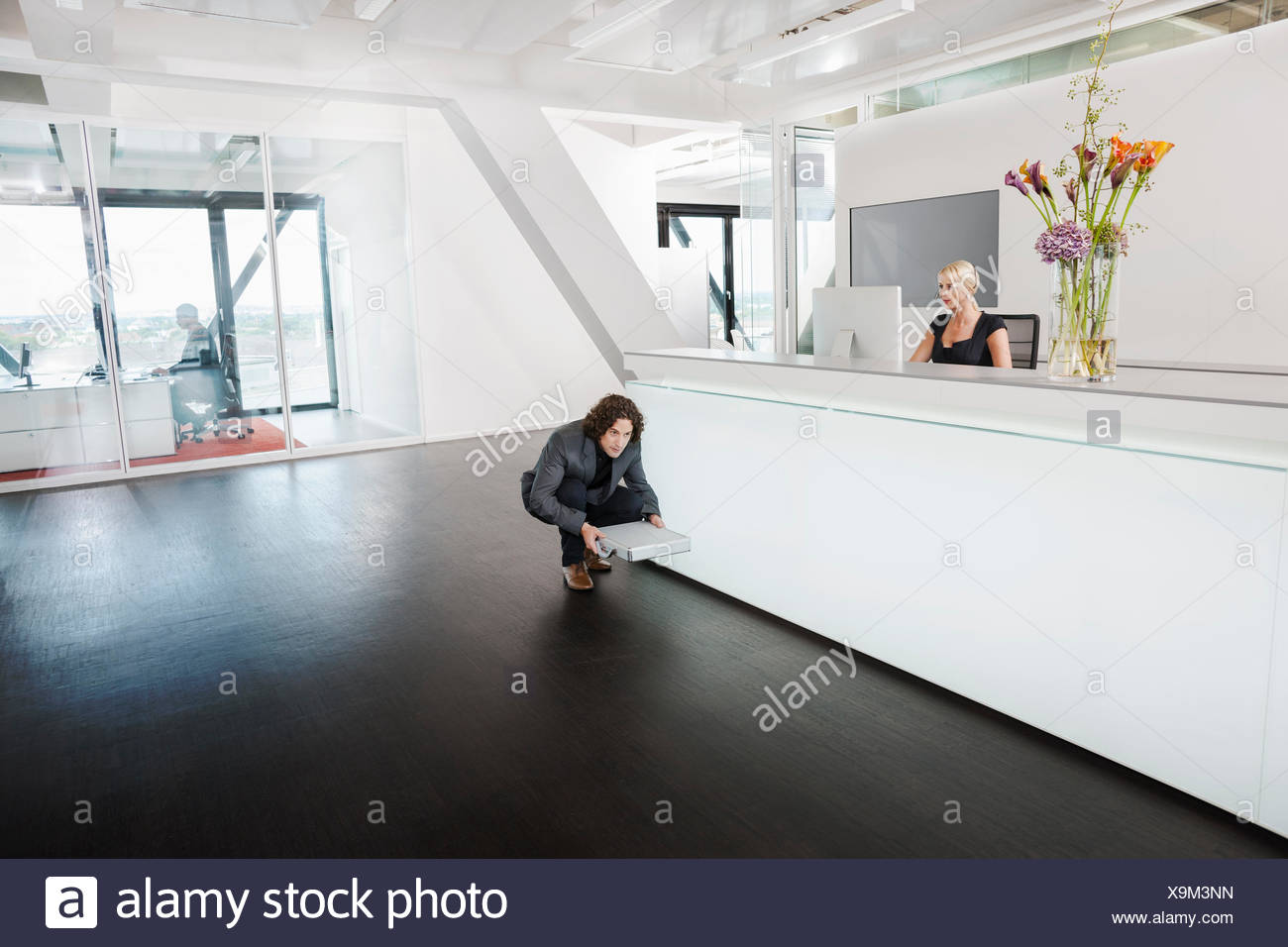 Man crouching in front of reception desk with briefcase - Stock Image