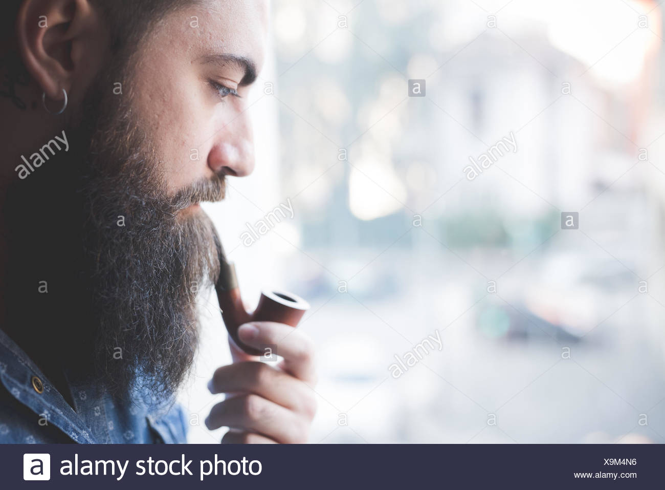 Young bearded man smoking pipe by window - Stock Image