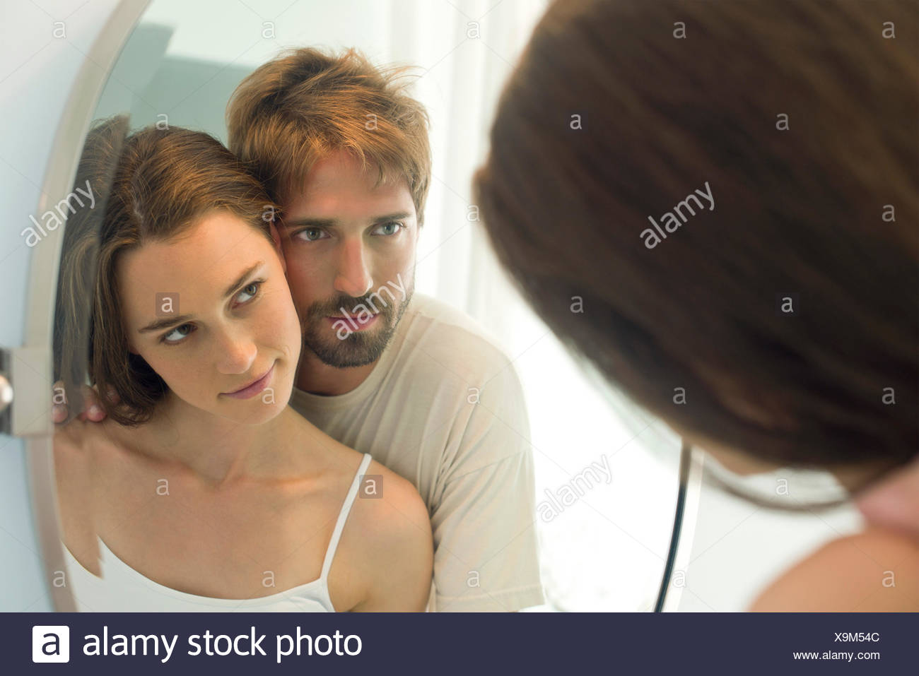 Couple cheek to cheek, looking at each other in mirror - Stock Image