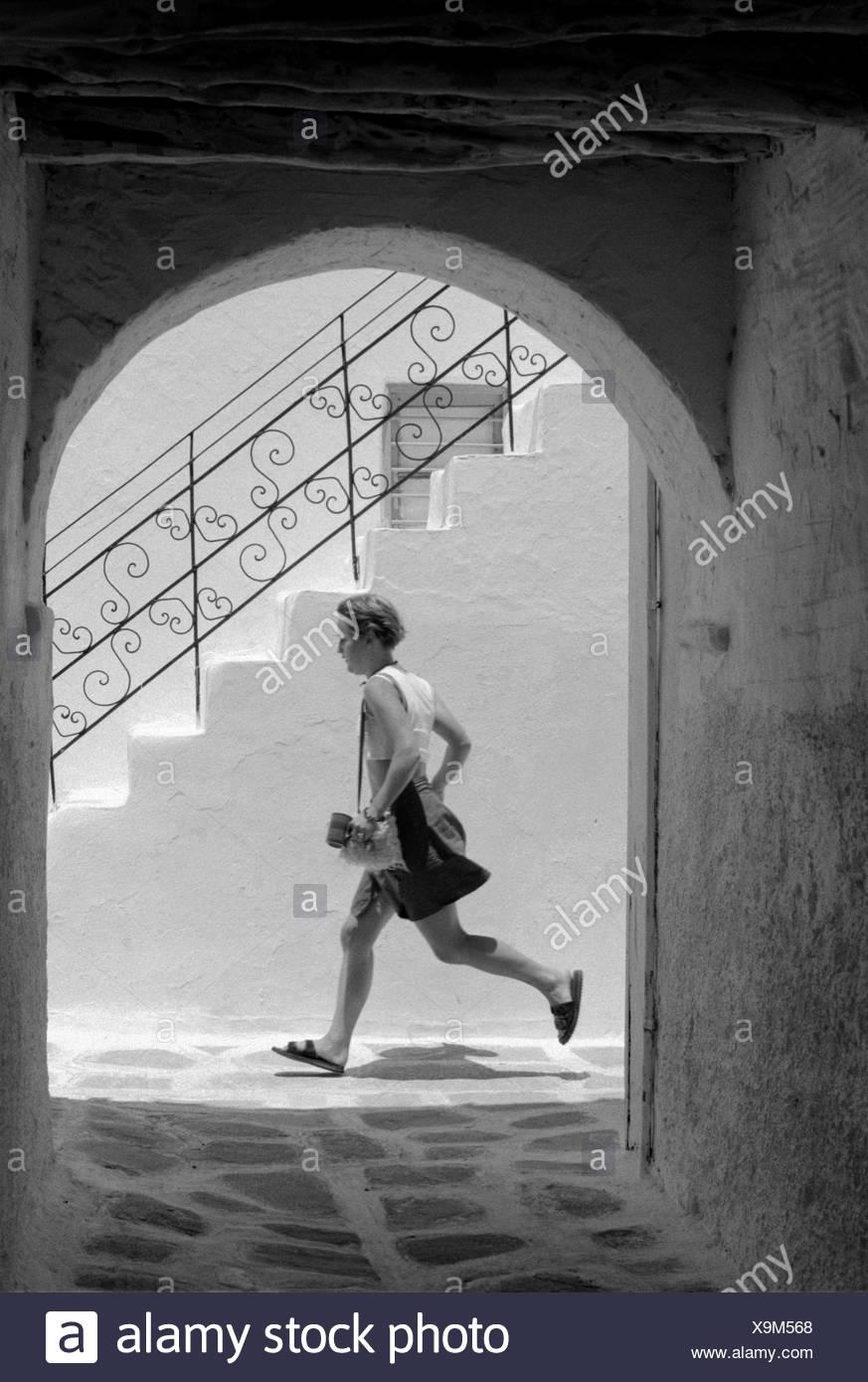 Griechenland, Kykladen, Insel Paros,  Gasse, Rundbogen, Mann, laufen, seitlich, s/w Kykladeninsel, Treppe, Stufen, Arkaden, Jogger,  Bewegung, sportlich, Eile, Hast, außen - Stock Image