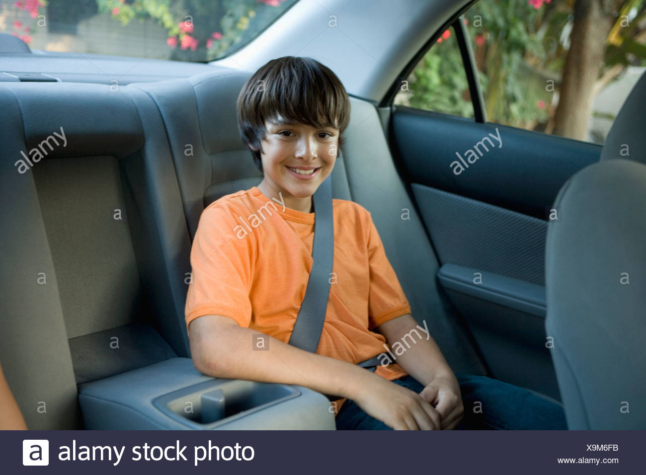 Boy sitting in back seat of car - Stock Image