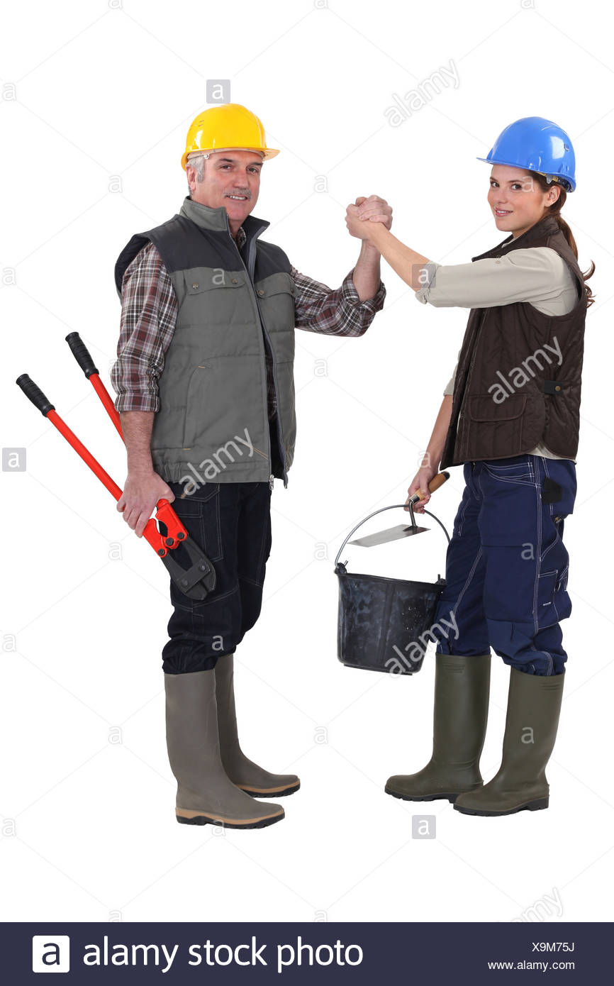Construction co-workers gripping hands - Stock Image