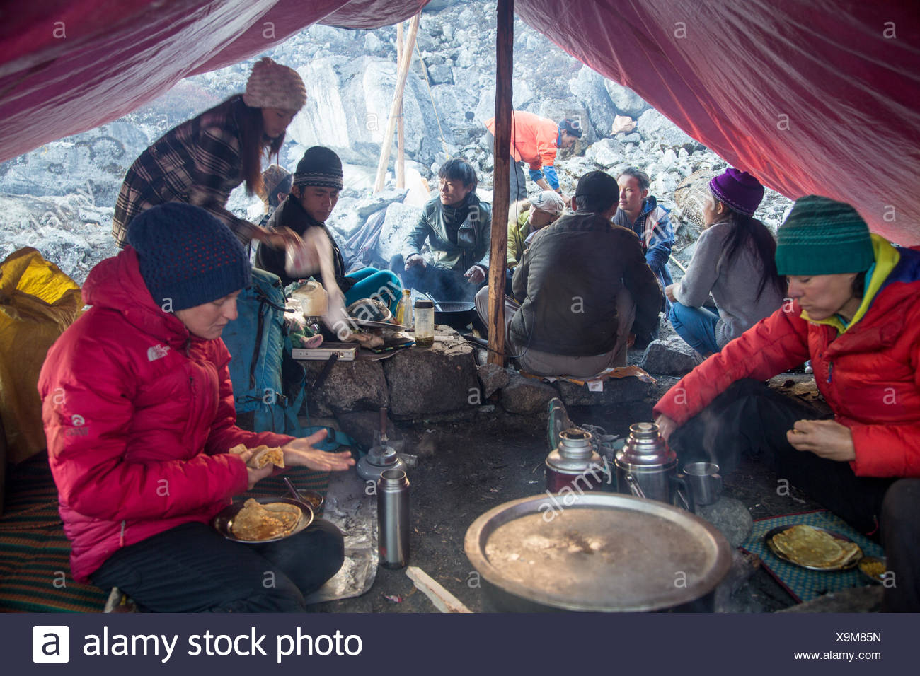 Porters and cooks eat breakfast before beginning the trek out from the Hkakabo Razi expedition's base camp. - Stock Image