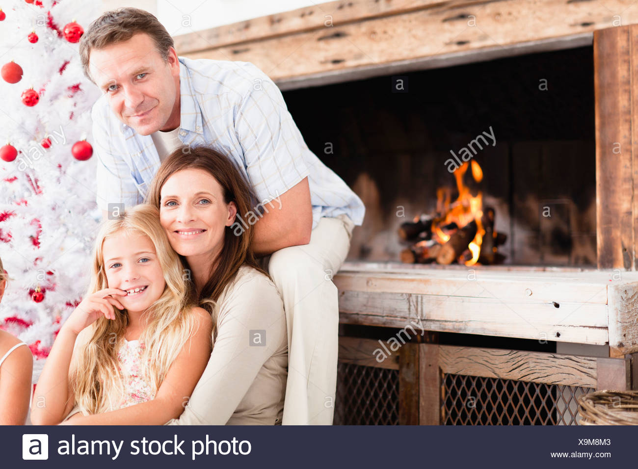 Family relaxing by Christmas tree Stock Photo