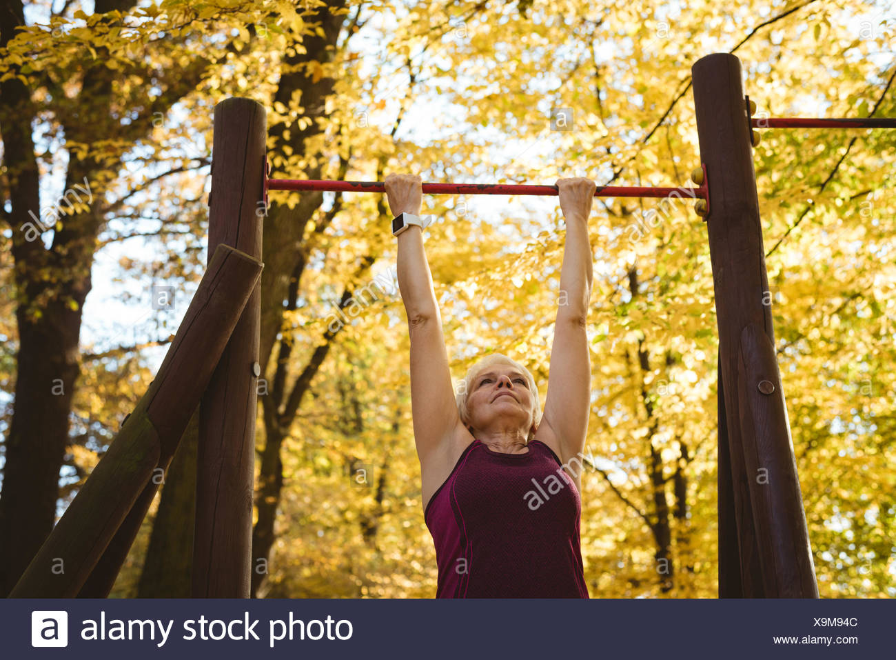 Senior woman practicing exercise in the park - Stock Image