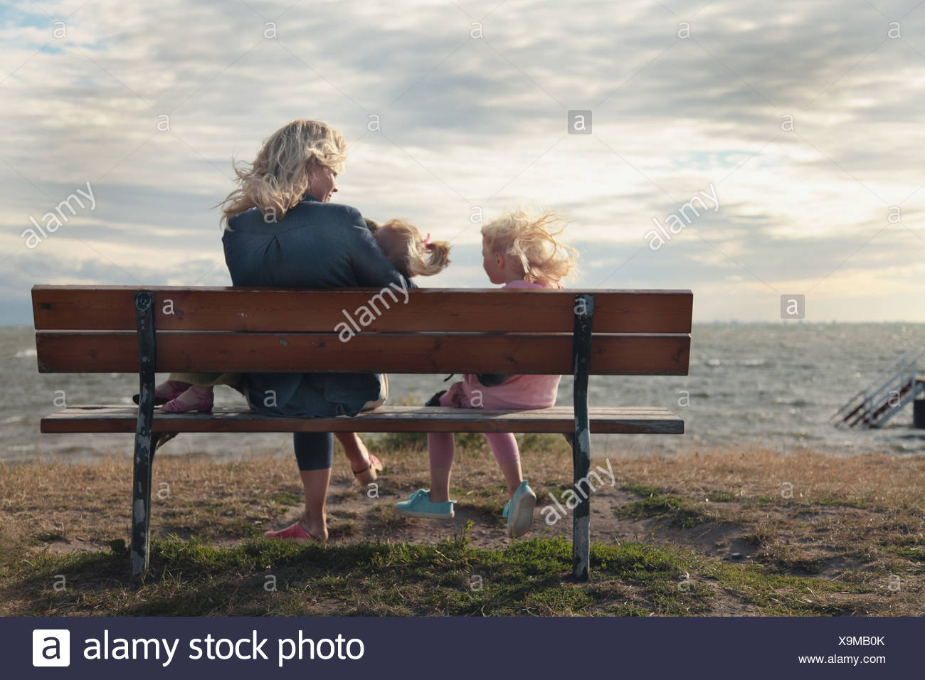 Woman and daughters (4-7) sitting on bench at beach Stock Photo