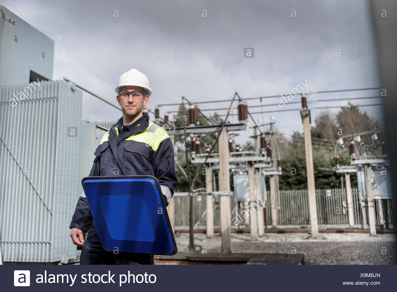 Worker using partial discharge detector in electricity substation - Stock Image