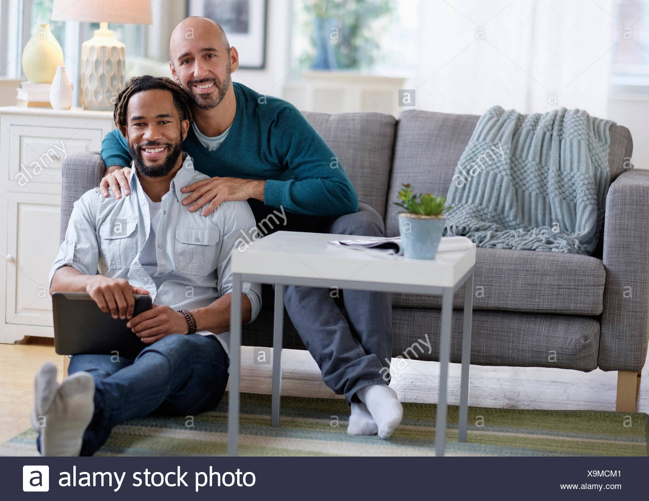 Man massaging boyfriend by sofa in living room - Stock Image