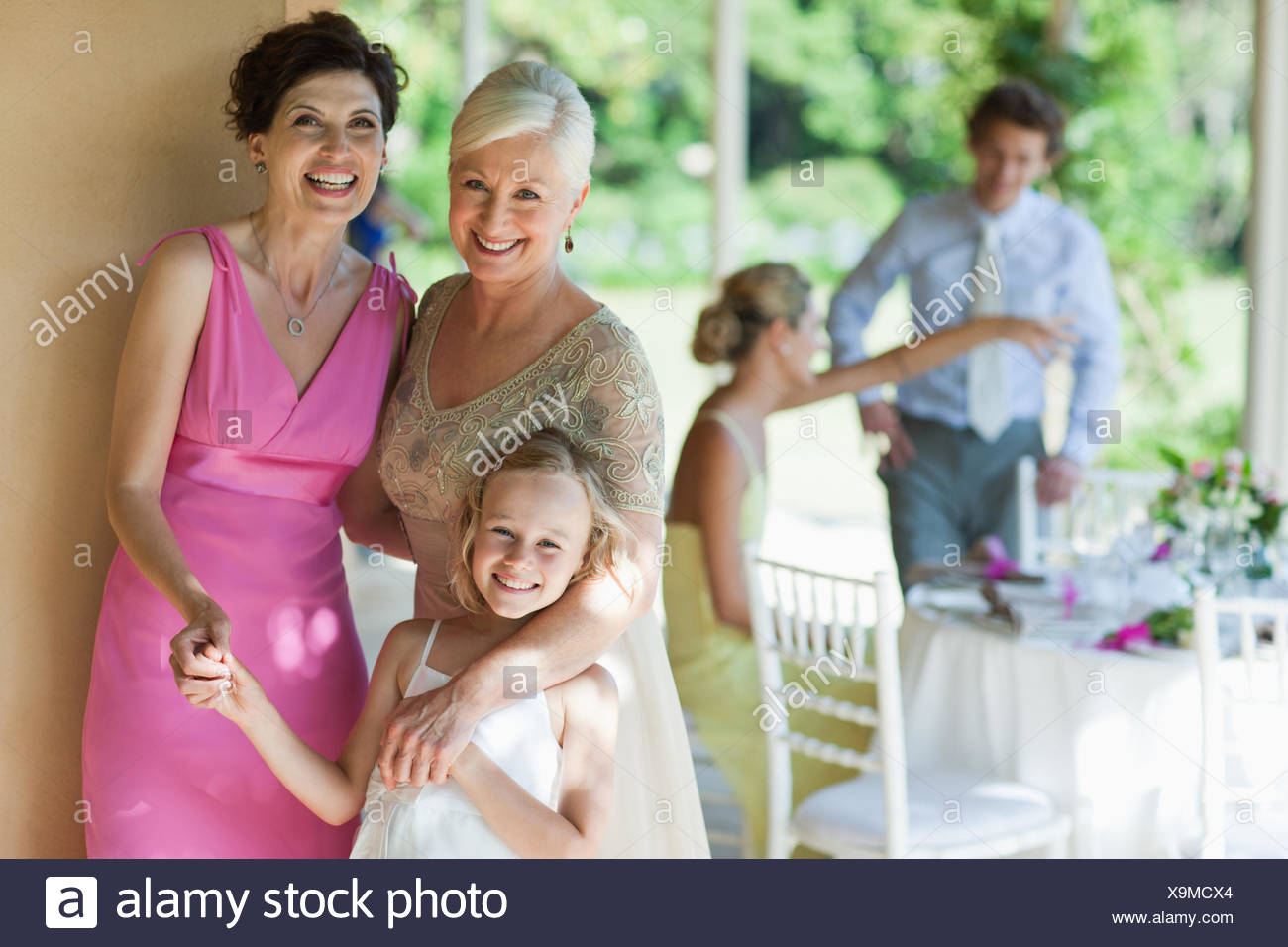 Family holding hands at wedding reception - Stock Image