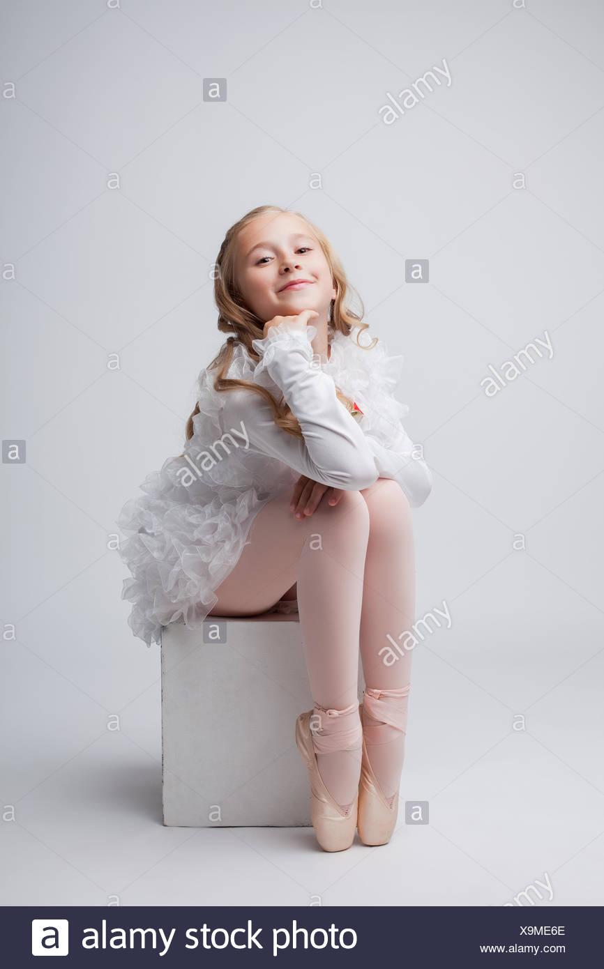 Coquettish little ballerina posing at camera - Stock Image