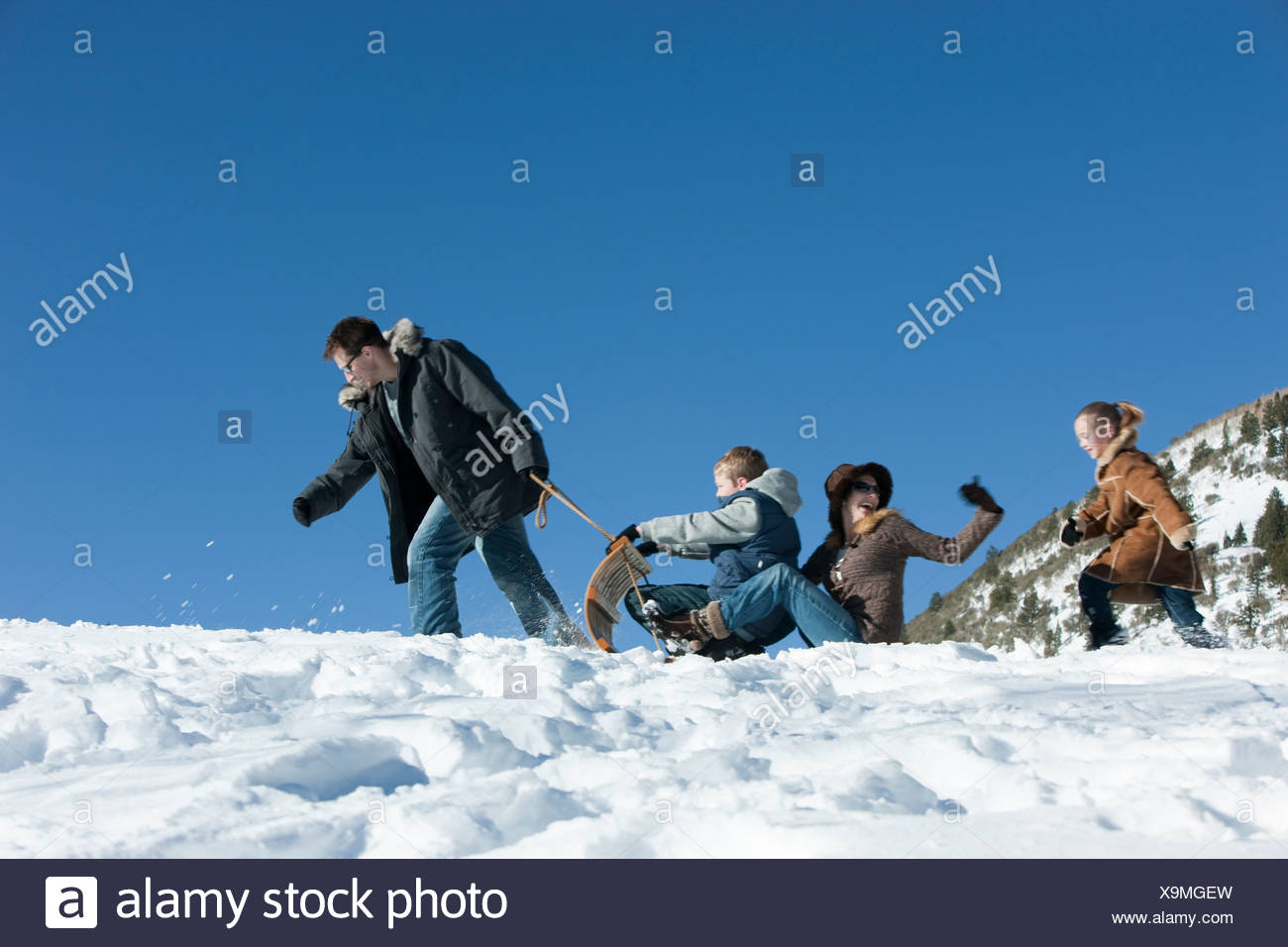 USA, Utah, Big Cottonwood Canyon, family tobogganing in mountains - Stock Image
