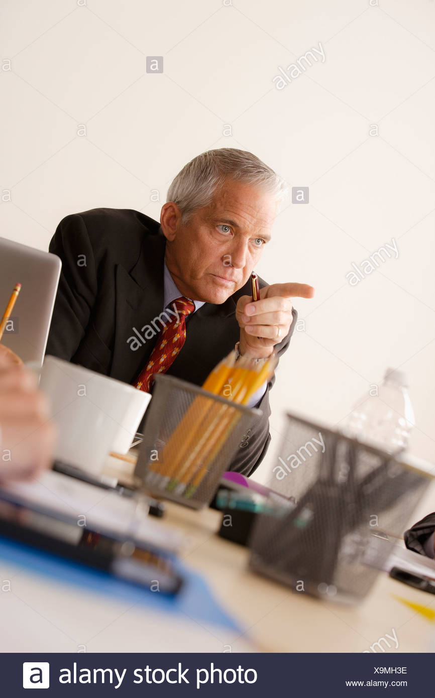 Businessman pointing finger from behind desk - Stock Image
