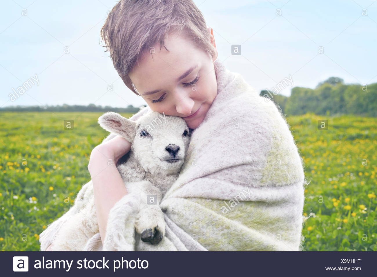 Portrait of young woman in field carrying lamb and wrapped in blanket - Stock Image