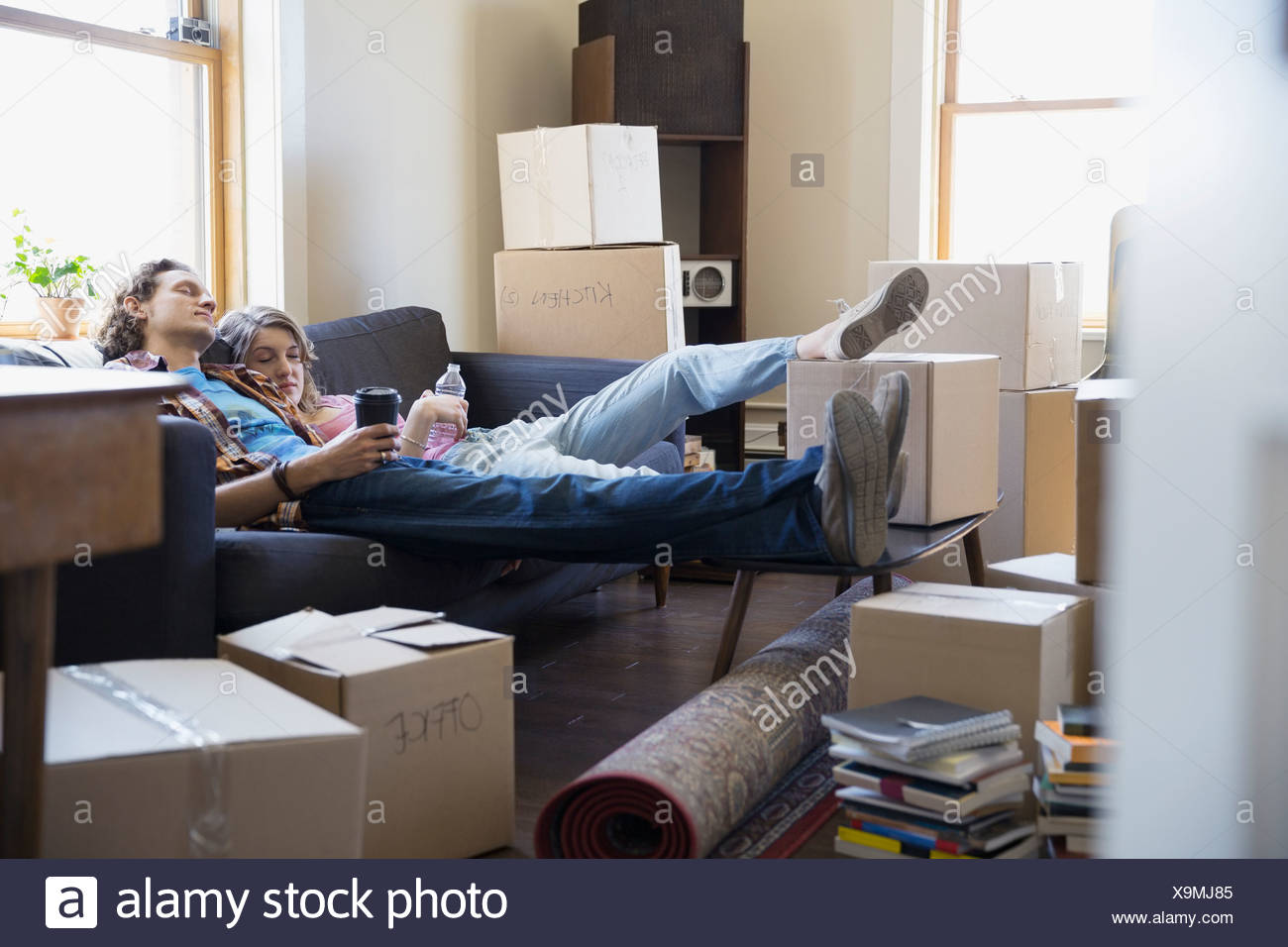 Couple relaxing on sofa surrounded by moving boxes - Stock Image