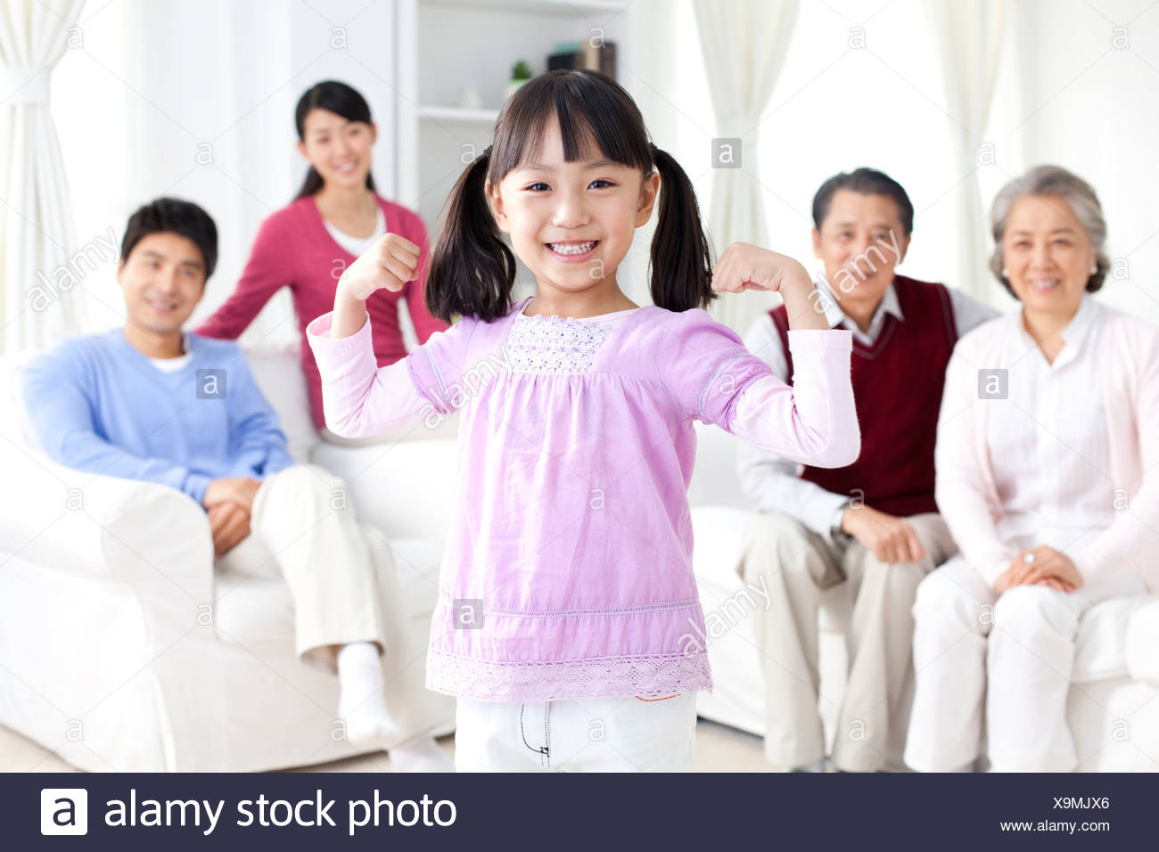 Young Chinese girl flexing myuscles, parents and grandparents behind her - Stock Image