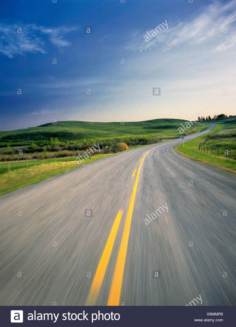 Road through pastureland near Cochrane, Alberta, Canada. - Stock Image