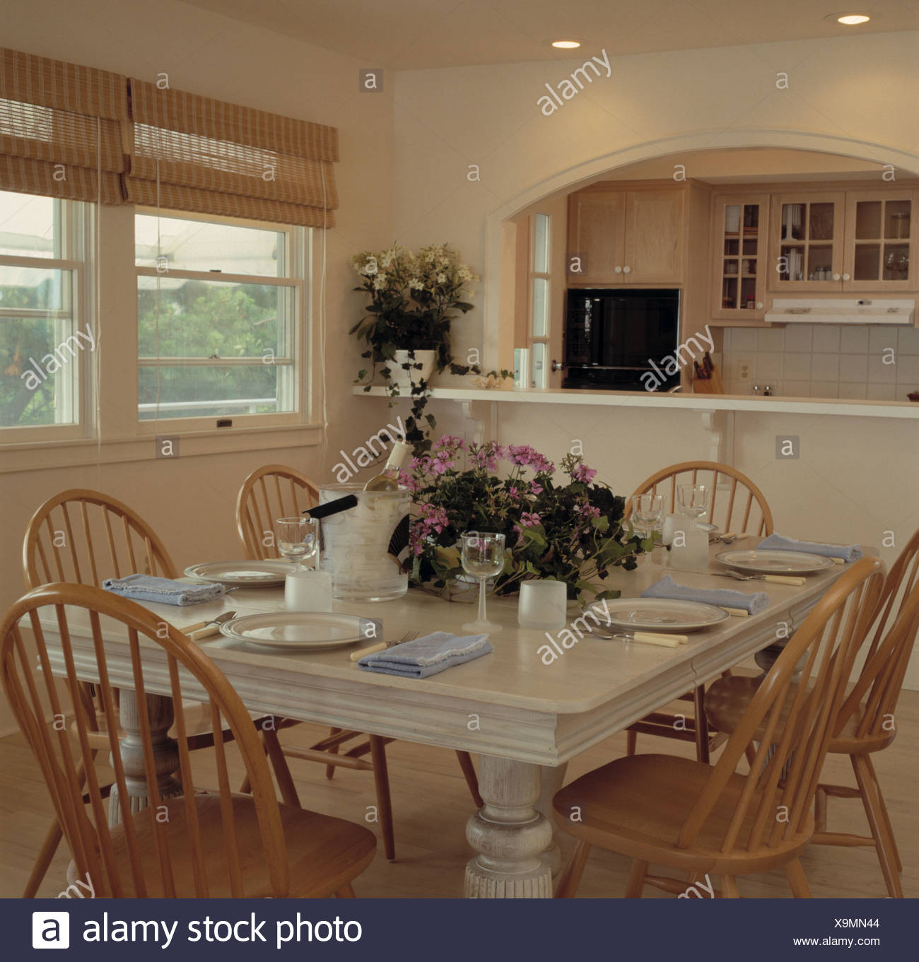 Flower arrangement and place settings on white table in dining room with Windsor chairs and split-cane blind on window & Flower arrangement and place settings on white table in dining room ...