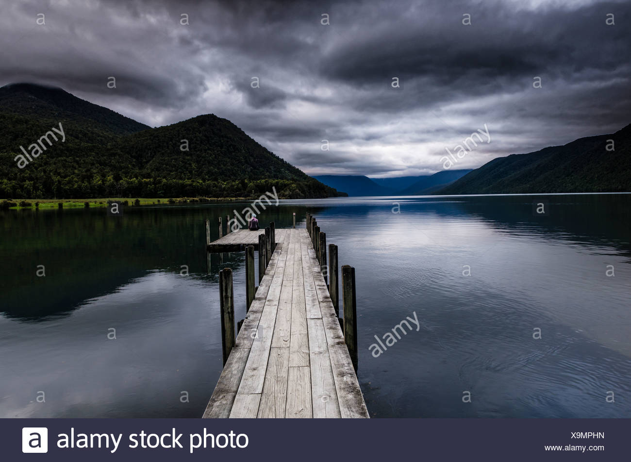 Woman sitting in a gloomy weather mood at the end of a wooden footbridge, Lake Rotoroa, South Island, New Zealand - Stock Image