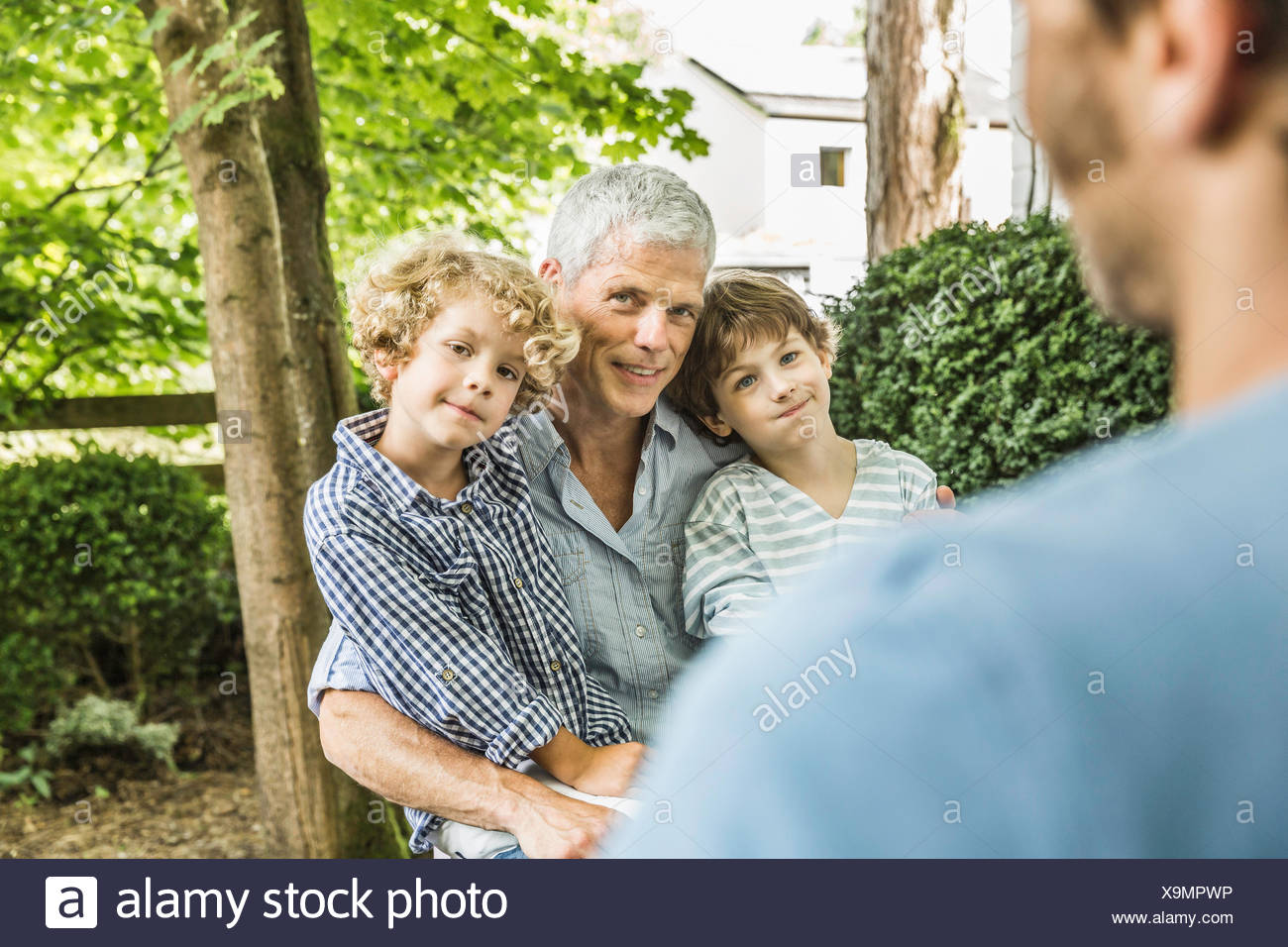 Mid adult man with father and sons in garden Stock Photo