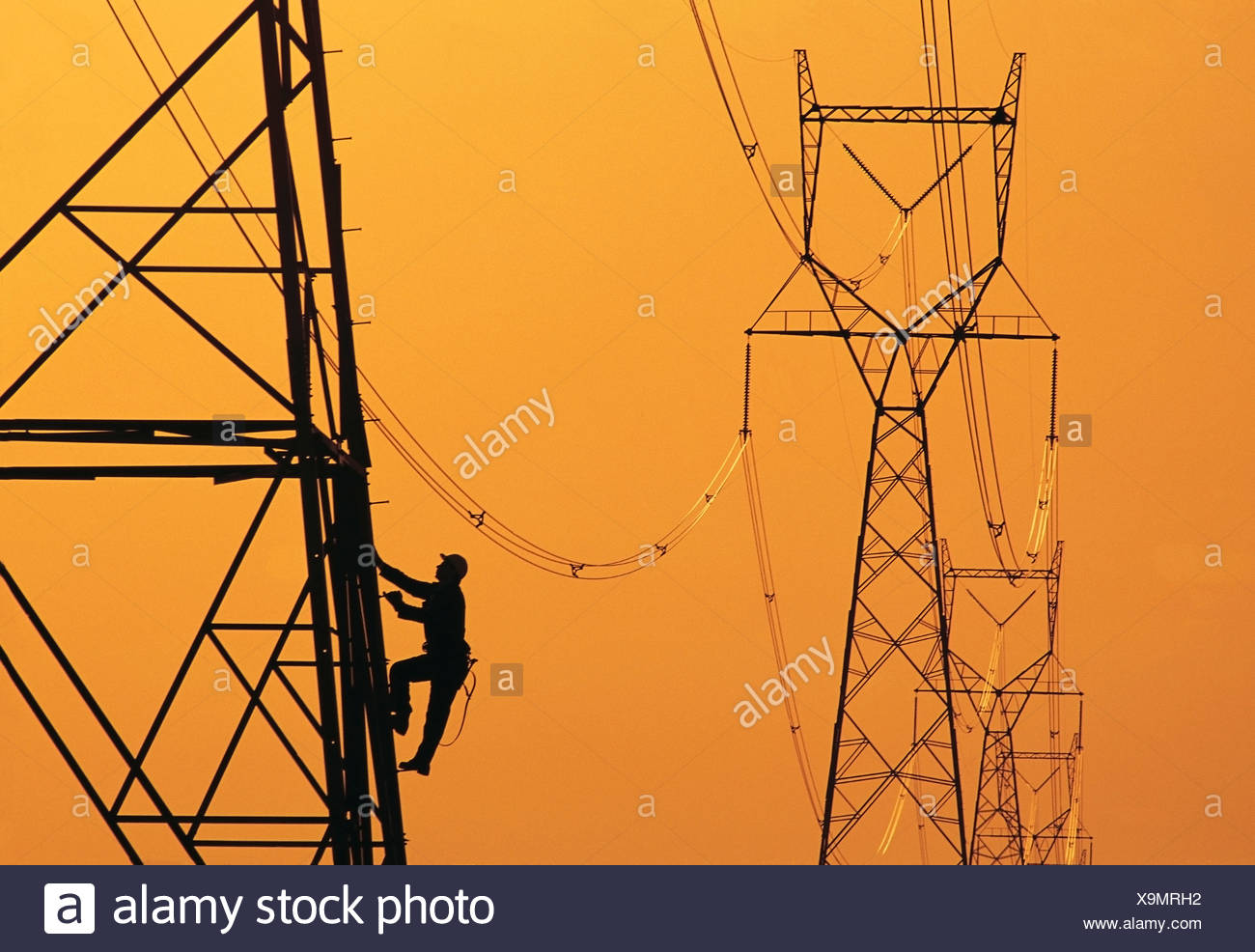 A worker climbs an electrical tower, Manitoba, Canada - Stock Image