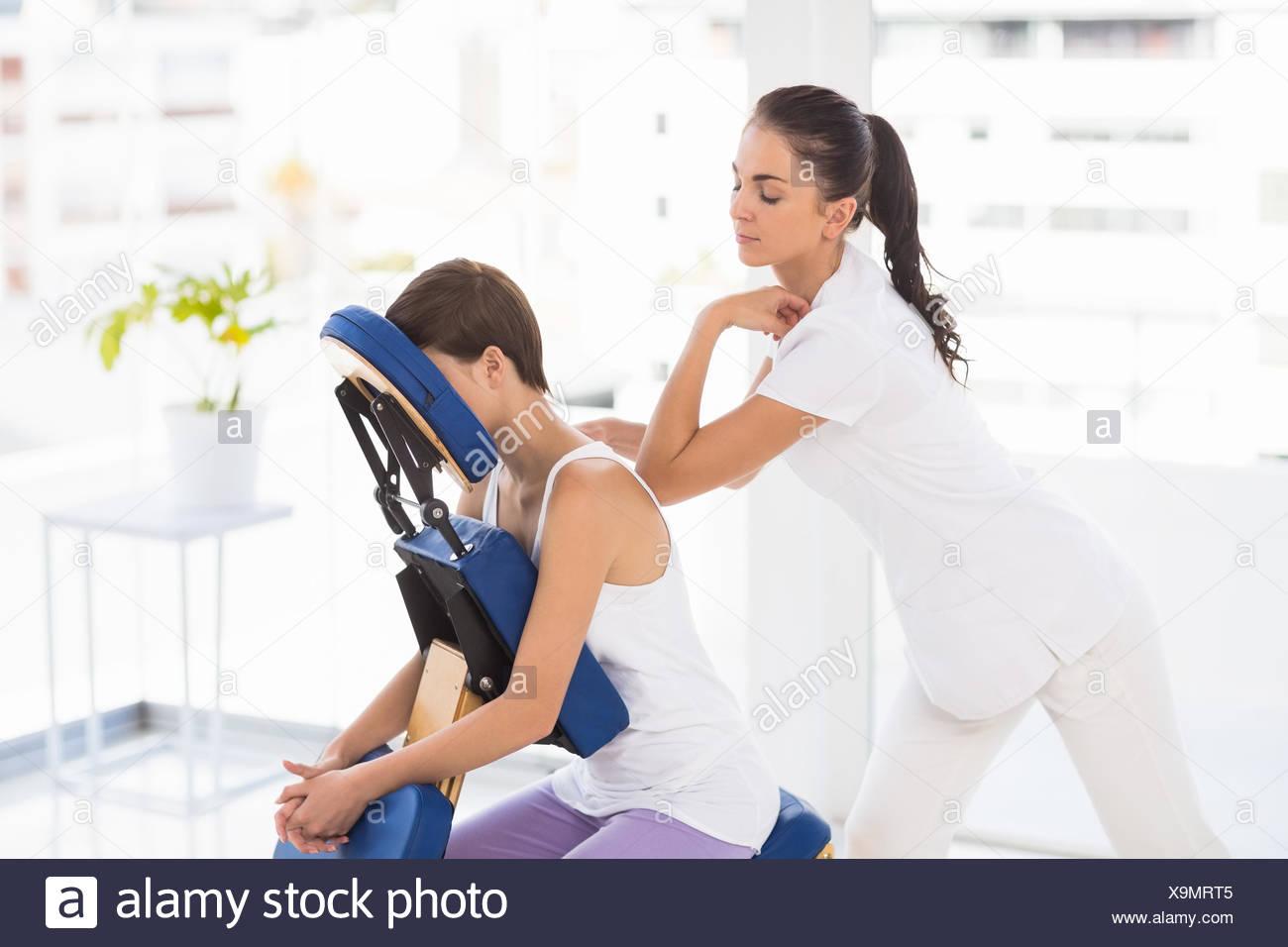 Masseuse giving back massage to woman - Stock Image