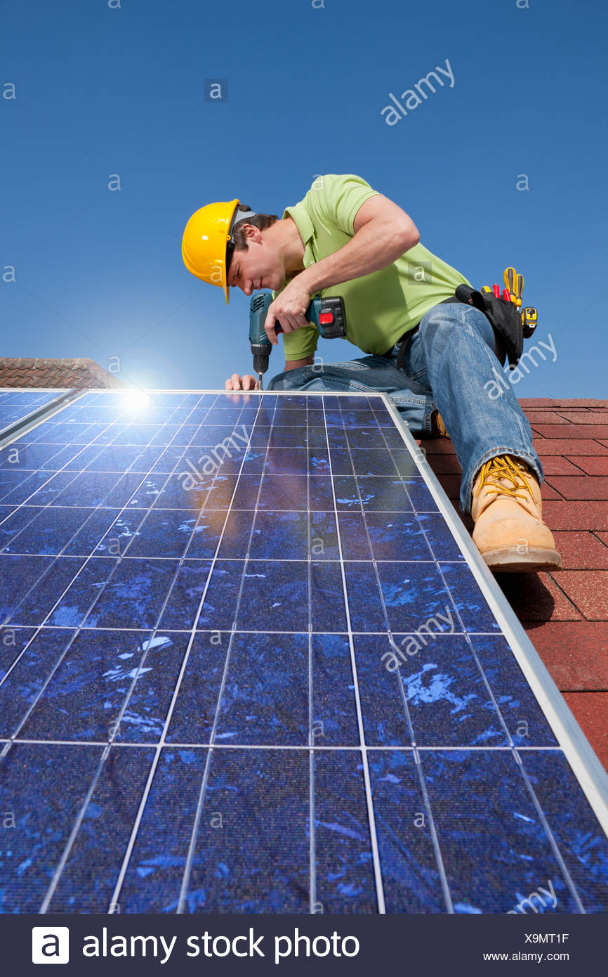 Engineer installing solar panel on rooftop with drill - Stock Image