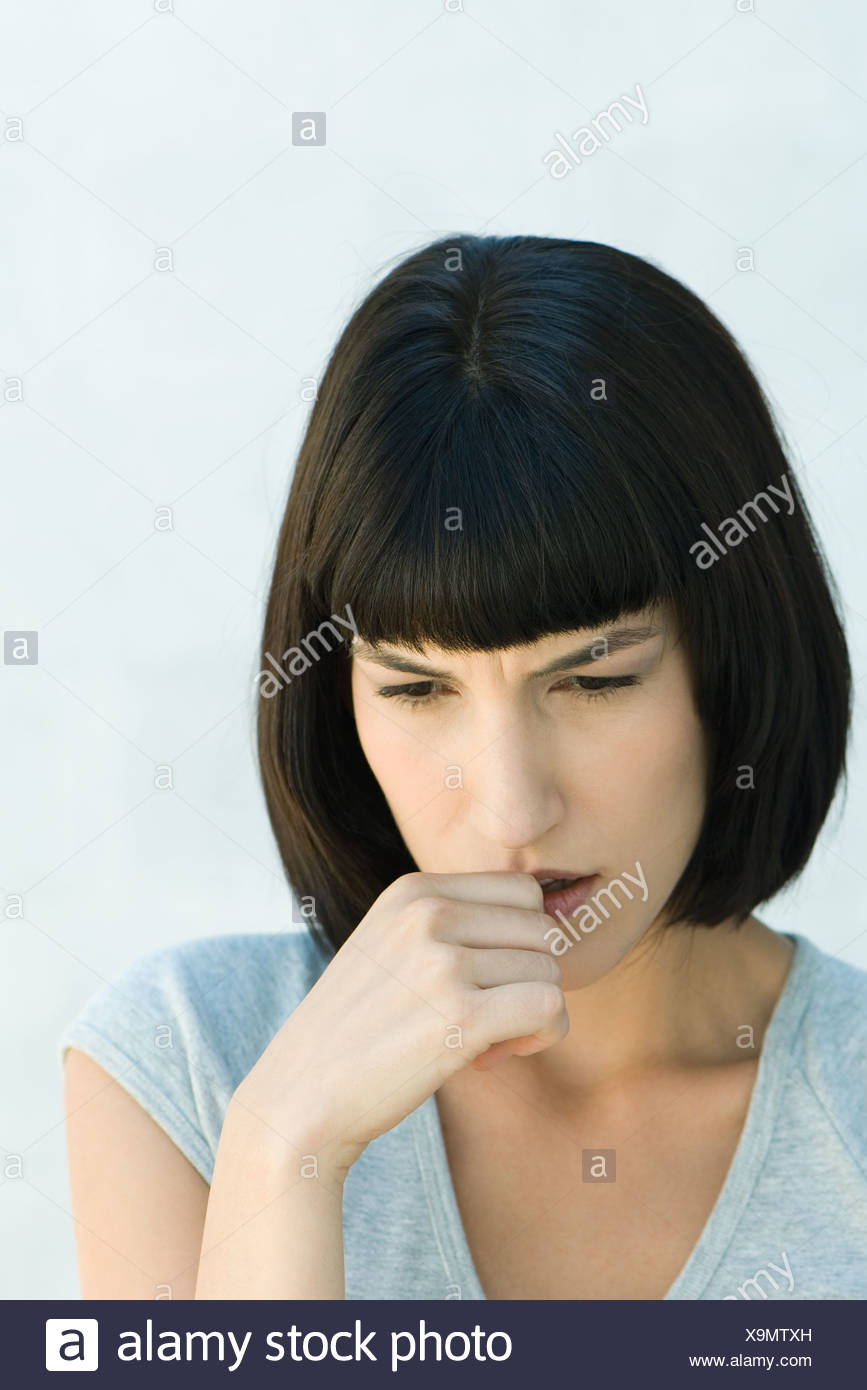 Woman biting thumb and looking down, head and shoulders, portrait Stock Photo